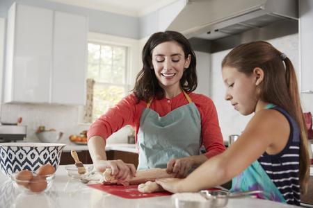 Photo pour Jewish mother and daughter rolling dough for challah bread - image libre de droit