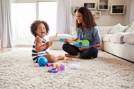Photo pour Young black mum plays ukulele with toddler daughter at home - image libre de droit