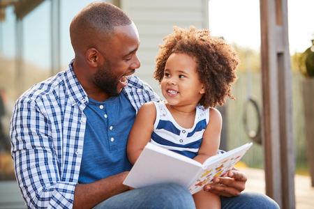 Photo pour Young black father and daughter reading book outside - image libre de droit