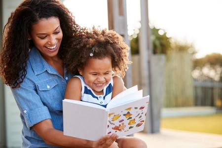 Photo pour Young black girl reading book sitting on mumÕs knee outdoors - image libre de droit