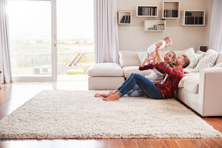 Photo pour Young white couple play with their toddler in sitting room - image libre de droit