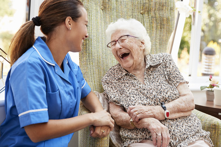 Photo for Senior Woman Sitting In Chair And Laughing With Nurse In Retirement Home - Royalty Free Image