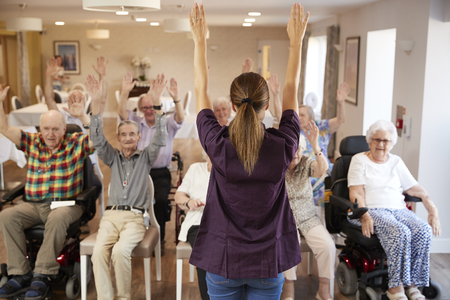 Photo pour Carer Leading Group Of Seniors In Fitness Class In Retirement Home - image libre de droit