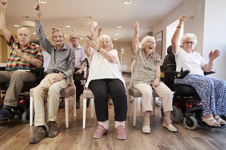 Photo pour Group Of Seniors Enjoying Fitness Class In Retirement Home - image libre de droit