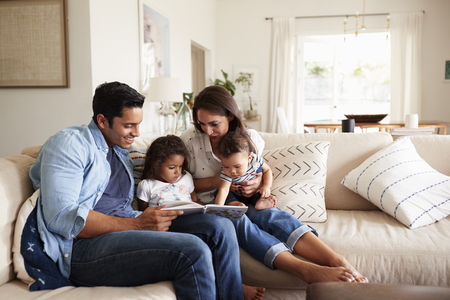 Photo pour Hispanic couple sitting on the sofa reading a book at home with their baby son and young daughter - image libre de droit