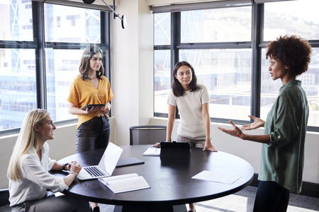 Photo for Female creatives in a meeting room listening to their colleague making an informal presentation - Royalty Free Image