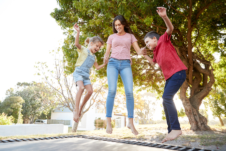 Photo pour Siblings With Teenage Sister Playing On Outdoor Trampoline In Garden - image libre de droit
