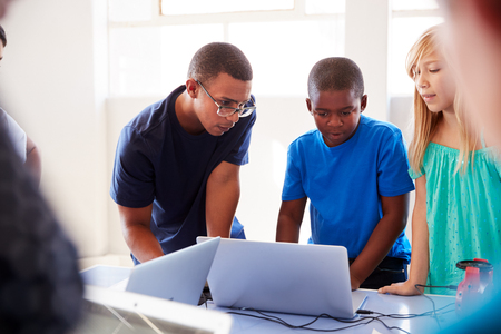 Foto de Group Of Students In After School Computer Coding Class Learning To Program Robot Vehicle - Imagen libre de derechos