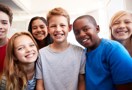 Photo pour Portrait Of Smiling Male And Female Students In Grade School Classroom - image libre de droit