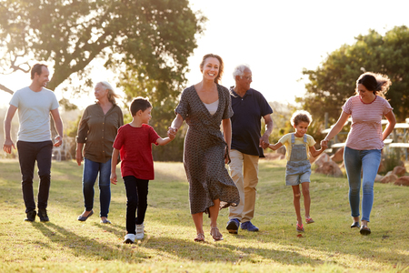 Photo for Multi-Generation Family Walking In Countryside Against Flaring Sun - Royalty Free Image