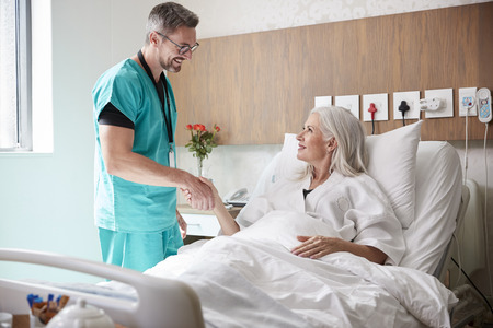 Photo pour Surgeon Visiting And Shaking Hands With Mature Female Patient In Hospital Bed - image libre de droit