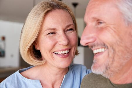 Photo pour Close Up Of Smiling Senior Couple Standing At Home In Kitchen Together - image libre de droit