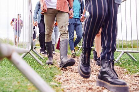 Photo for Close Up Of Friends At Entrance To Music Festival Walking Through Security Barriers - Royalty Free Image