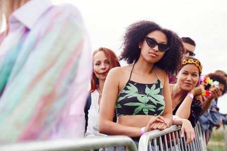 Photo for Group Of Young Friends Waiting Behind Barrier At Entrance To Music Festival Site - Royalty Free Image