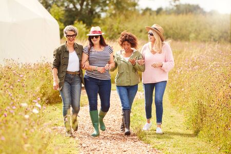 Photo for Group Of Mature Female Friends Walking Along Path Through Yurt Campsite - Royalty Free Image