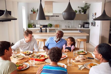 Photo pour Multi-Generation Mixed Race Family Eating Meal Around Table At Home Together - image libre de droit