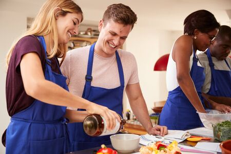Photo for Male And Female Adult Students Adding Olive Oil To  Dish In Kitchen Cookery Class - Royalty Free Image