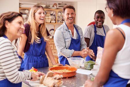 Foto de Male And Female Adult Students Preparing Ingredients For Dish In Kitchen Cookery Class - Imagen libre de derechos
