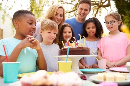 Photo pour Parents And Son Celebrating Birthday With Friends Having Party In Garden At Home - image libre de droit