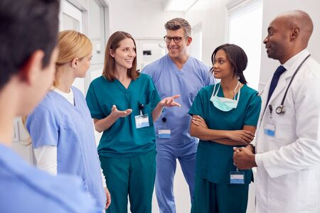 Photo for Multi-Cultural Medical Team Having Meeting In Hospital Corridor - Royalty Free Image