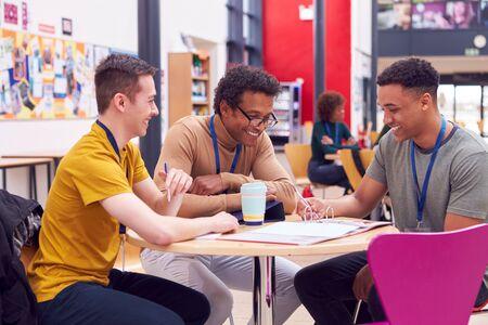 Foto de College Student Meeting With Male Tutor In Busy Communal Campus Building - Imagen libre de derechos