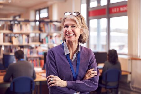 Photo for Portrait Of Mature Female Teacher Or Student In Library With Other Students Studying In Background - Royalty Free Image