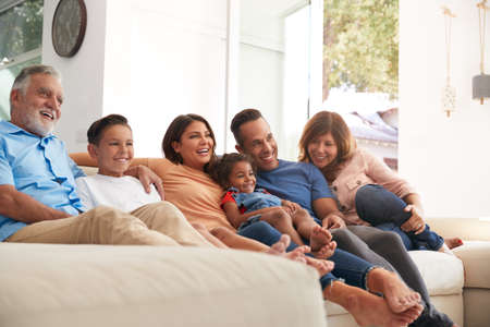 Photo pour Multi-Generation Hispanic Family Relaxing At Home Sitting On Sofa Watching TV Together - image libre de droit