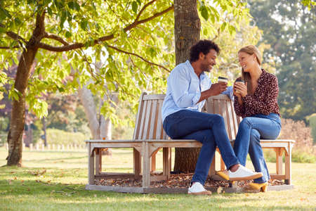 Photo for Loving Mature Couple Relaxing Sitting Together On Bench Under Tree In Summer Park With Coffee - Royalty Free Image