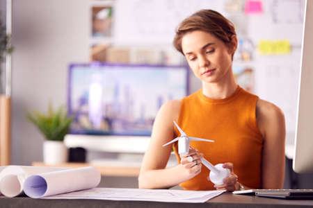 Photo for Female Architect In Office Working On Drawings For Renewable Energy Project With Model Wind Turbine - Royalty Free Image