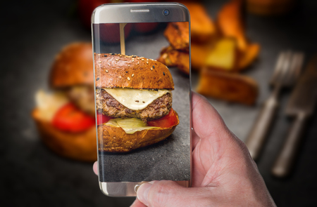 Photo pour Man taking photo of Traditional Cheeseburger with beef meat and fried potato - image libre de droit