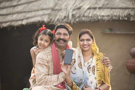 Foto per Delighted rural family holding new mobile phone - Immagine Royalty Free