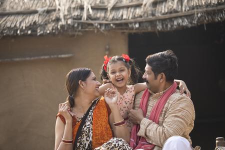 Foto de Indian family sitting on traditional bed in village - Imagen libre de derechos