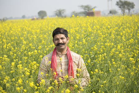 Foto de Indian farmer standing in agricultural field - Imagen libre de derechos