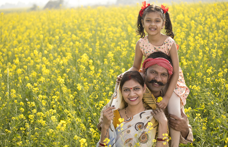 Photo pour Portrait of happy rural family in rapeseed agricultural field - image libre de droit