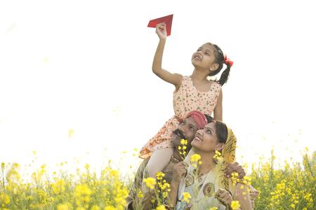 Foto de Girl sitting on fathers shoulder and throwing paper airplane - Imagen libre de derechos