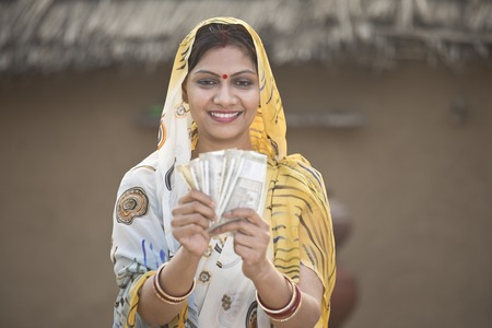 Foto de Excited woman holding Indian rupee notes and screaming - Imagen libre de derechos