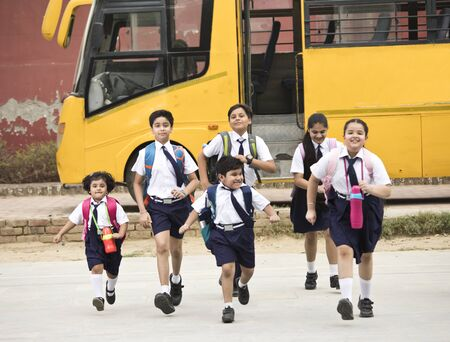 Photo pour Schoolboys and schoolgirls walking of the school bus - image libre de droit