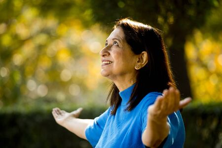 Photo for Senior woman with arms outstretched at park - Royalty Free Image