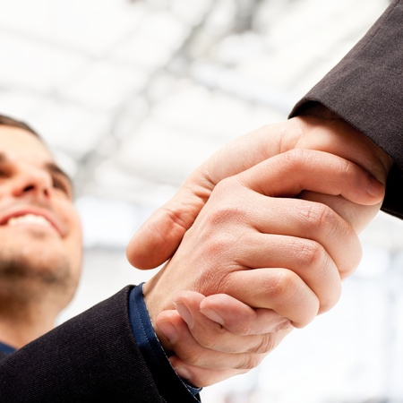 Business people shaking hands  Bright blurred background