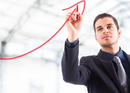 Businessman drawing a rising arrow, representing business growth.