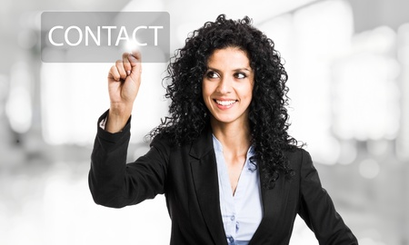 Beautiful businesswoman touching a contact button on the screen