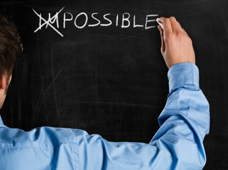 Man turning the word  Impossible  into  Possible