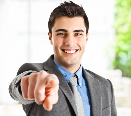 Handsome smiling businessman pointing his finger to you