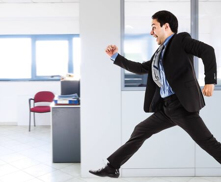 Portrait of an active businessman running in his office