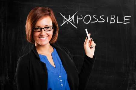Smiling teacher turning the word impossible into possible