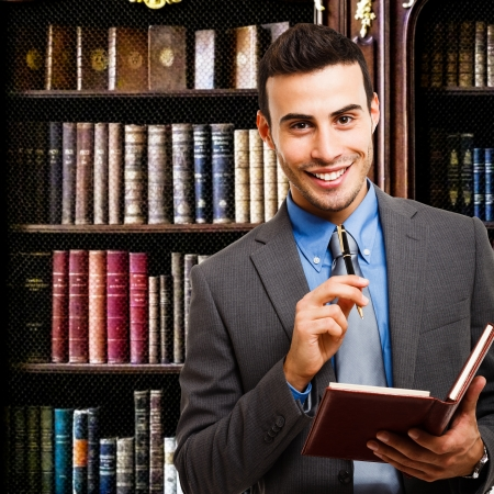 Portrait of a smiling businessman holding an agenda