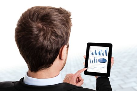 Businessman monitoring stock market graphs on his tablet