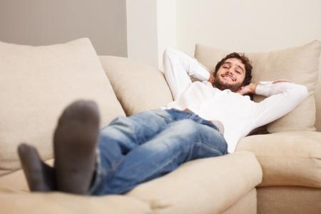 Photo pour Young man relaxing on his couch - image libre de droit