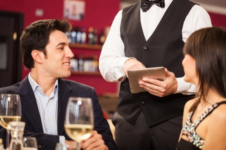 Waiter using a digital tablet to take an order