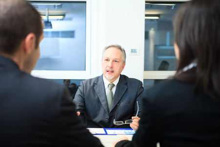 Photo pour Businessman talking to a couple in a office - image libre de droit